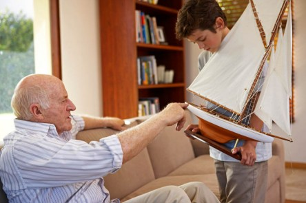 Grandfather and grandson enjoying time together with model boat