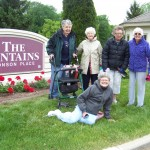 Residents pose for a picture in front of our fountains entry sign.