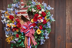 A close up of an Fouth of July wreath haning on a wood fence.