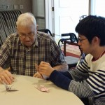 Bill learns to make an origami crane with a student from Japan.
