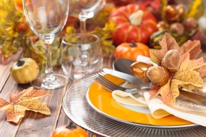 Autumn place setting with leaves, candles and pumpkins.