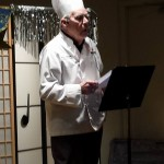 John Whitlock performs his humorous essay, The Culinary Klutz, garbed in dining jacket and chef's hat.
