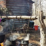Mary Jo and Phyllis study the syrup-making process as kettles boil outside a log cabin on the DeLano farm.
