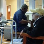 Two residents tapping their feet to the rhythm of the guest piano player.