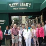 30 residents from the Fountains at Bronson Place and The Fountains at Crystal Lake gather at the entrance of Harry Caray's Italian Steakhouse in Chicago.