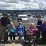 Gardens residents and associates pose for a photo at the marina outside Clementine's II in St. Joseph, Michigan.