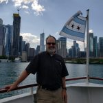 Our driver poses with the Chicago flag at the stern of the boat.