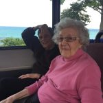 Residents smiling as Lake Michigan shows through the windows of the bus.