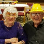 Couple in hats and glasses enjoying the party.