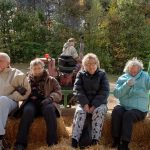 A group of residents at the front end of the hay wagon traveling through the orchard.