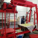 A cider mill employee spreading apple pulp on the press.