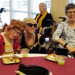 Inn residents enjoying the party with Community Life Assistant Jennifer as Holly Go-Frightly