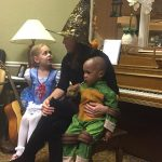 Music therapist in witch hat with children dressed as Dorothy and a Ninja Turtle