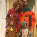 Group of family members dressed in costumes as pumpkin, clown, Scooby Doo and a shark
