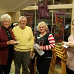 Dining staff enjoy a moment with a resident couple in the Town Center lobby