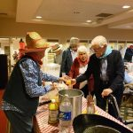 Committee member serves moonshine to residents at the buffet