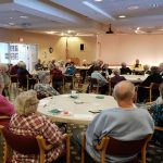 A large group of residents enjoying the program and refreshments at the party