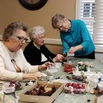 Three ladies work on making beautiful lace-topped winter candle holders.