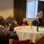 Residents at tables sharing stories and enjoying refreshments