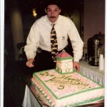 Andy (with a mustache) from with a cake from Bronson's five year anniversary party.