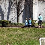 Children with their grandmother hunting for eggs in the courtyard