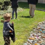A boy placing a colored egg in his bag, gazing out over a stone path covered with eggs!
