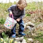 A child with his Easter bucket spies an egg while placing one in his bucket