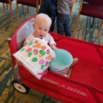 Toddler playing with Easter buckets in a wagon