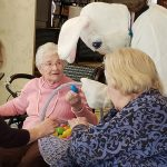 Easter bunny passing out eggs to residents