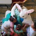Overhead view of children in a group hug with the Easter Bunny