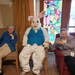 Two residents sit beside the Easter Bunny posing for a photo