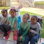 Easter Bunny nearly invisible behind a group of kids sitting on his lap