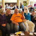 Residents with their daughter and grandson sitting on a couch with the Easter Bunny