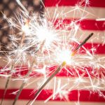 sparklers with American flag in the background